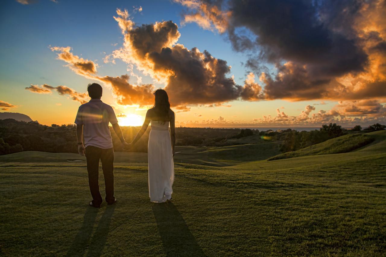 Couple holding hands walking toward sunset