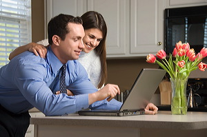 happy couple looking at something on laptop