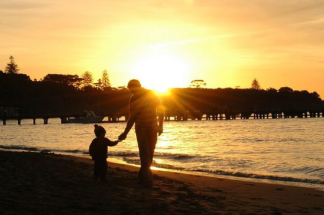Father and son on beach at sunrise