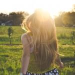 Girl running happily into beautiful sunny field.