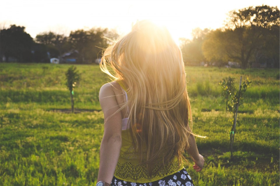 Girl running happily into beautiful sunny field.